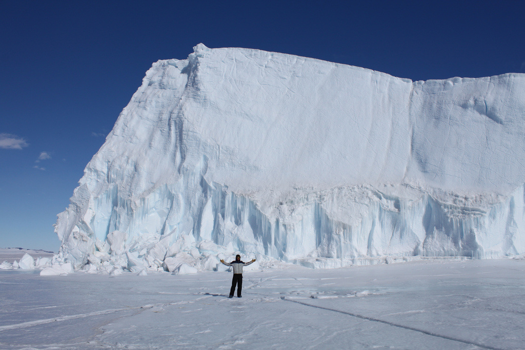 Iceberg with man standing in front of it on sheet ice with his arms extended out horizontally